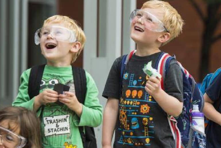 Curious Minds students wearing protective goggles while looking at the sky with wonder