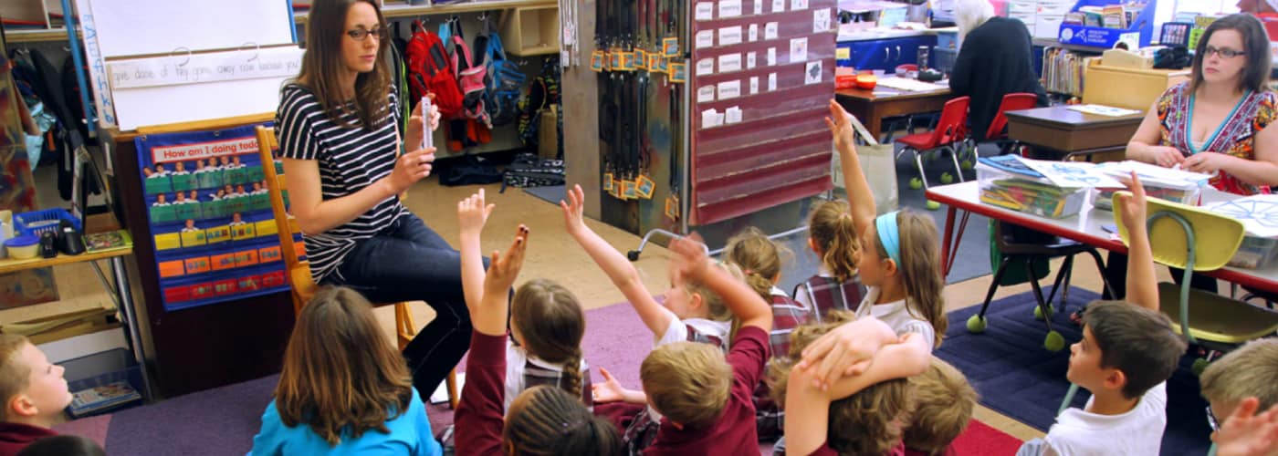 First grade students raising their hands to answer a Curious Minds instructor