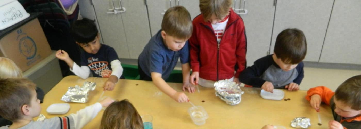First graders sitting at a table doing an experiment