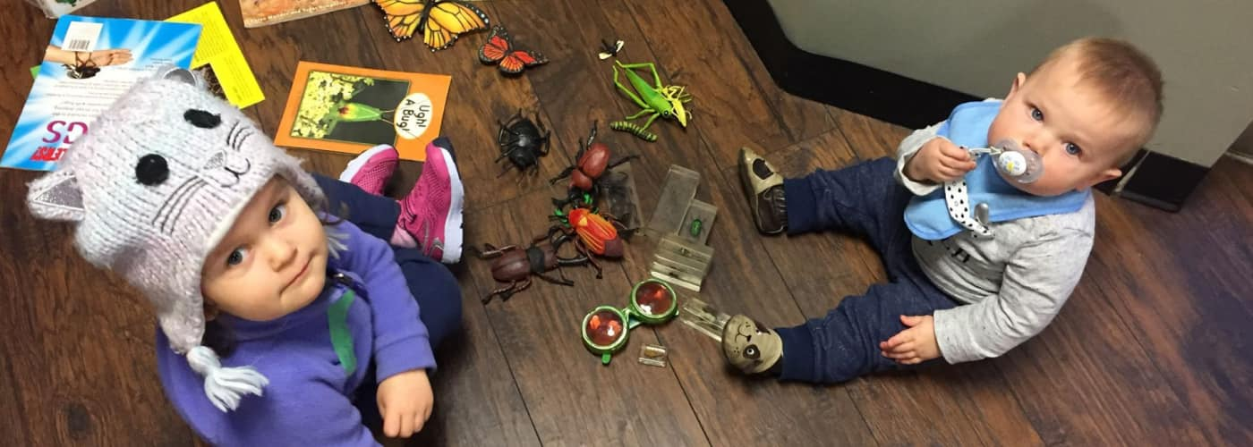 A toddler wearing a cat hat and playing with plastic bugs and butterflies